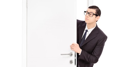 Businessman peeking through an opened door isolated on white background